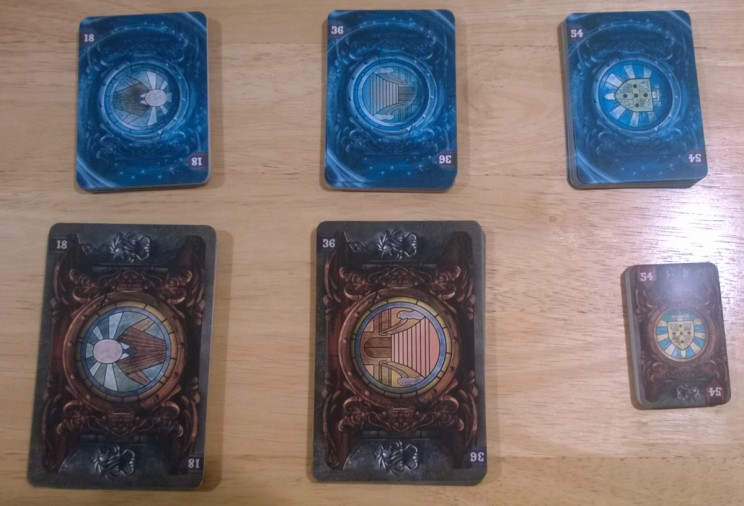 The small blue decks go to the Ghost and the larger decks are placed in play for the clairvoyants to observe.